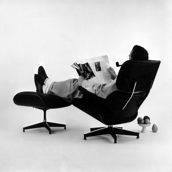 Charles Eames posing in the Lounge Chair, photo for an advertisement, 1956 © Eames Office LLC