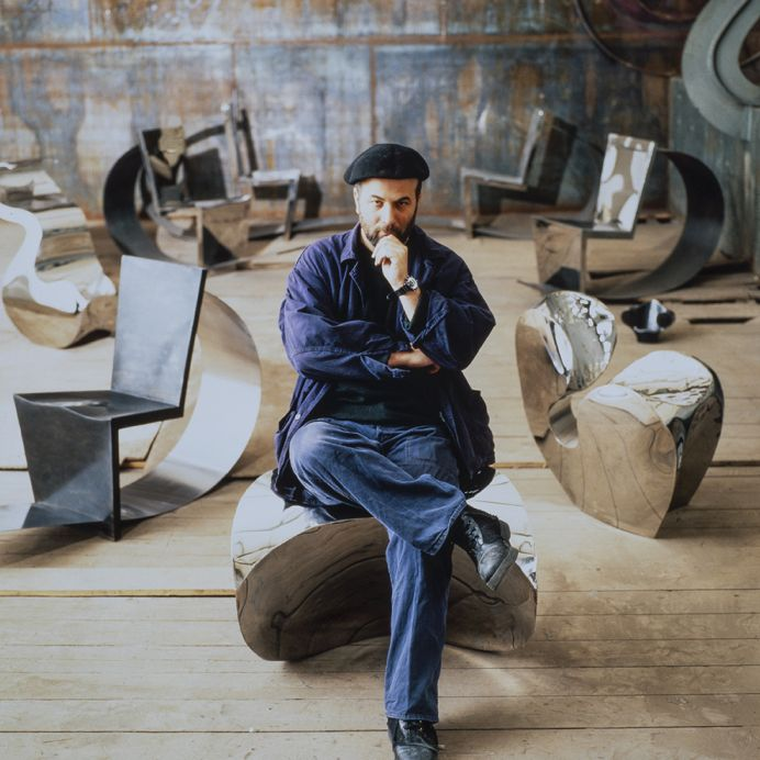 Ron Arad, 1991, sitting on Big Heavy (1989), in the background Rietveld Chair (1990) and Little Heavy (1989). © Vitra Archive