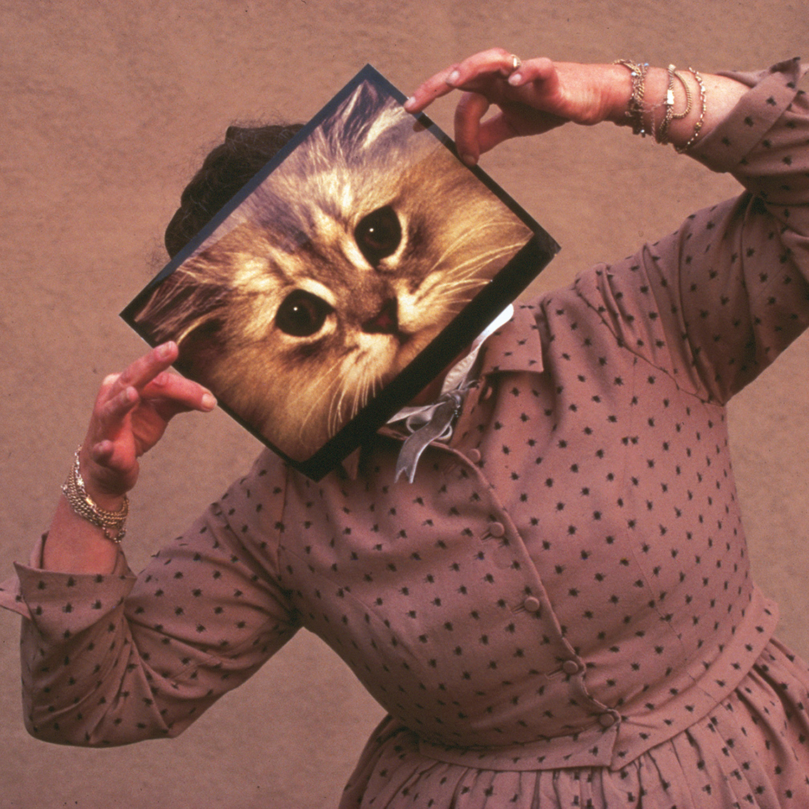 Ray Eames posing with a cat photograph, December 1970 © Eames Office LLC